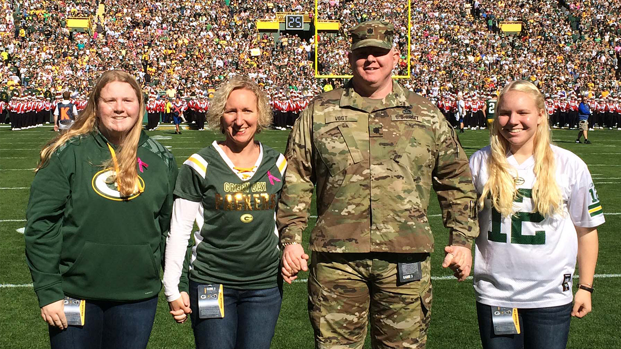 Standing on the field for the Operation Fan Mail presentation are Lt. Col. Brian Vogt, his wife, Kimberly, and daughters, Allison (left) and Emily (right).