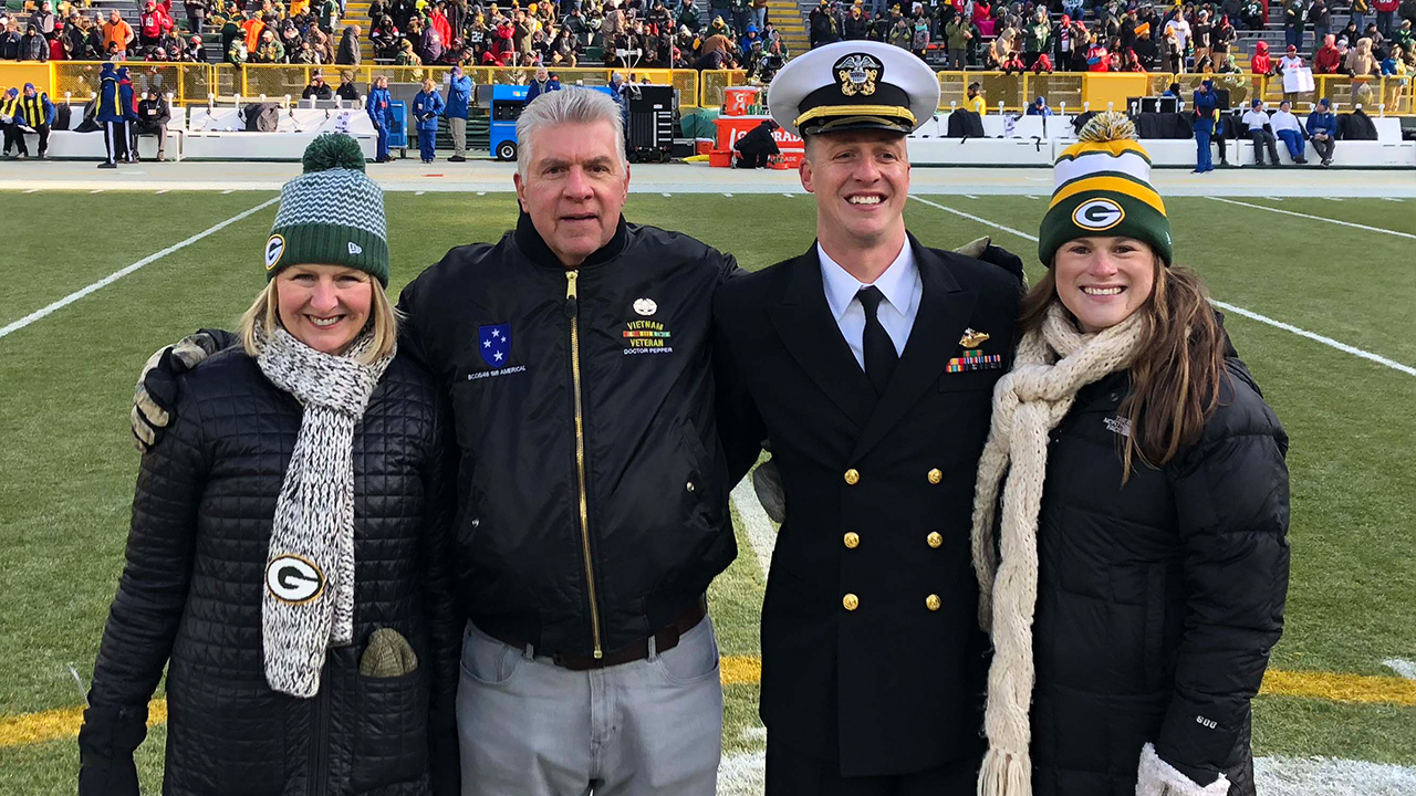 Lieutenant Max Hofer is shown on the field with his mother, Beverly; father, John; and wife, Molly.